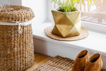 Hardwood floor with jute doormat, shoes and flower pot and seagrass laundry basket by window. Natural material objects in home concept. Home interior.